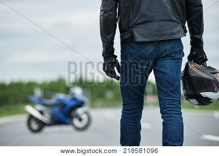 Transport gear speed power extreme hobby and urban lifestyle concept. Picture of good-looking serious unshaven young man in white t-shirt and jeans resting on asphalt next to his blue motorbike