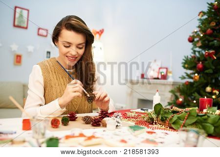 Attractive dark-haired woman wearing knitted vest sitting at desk of cozy living room decorated for Christmas celebration and coloring pinecone with gouache
