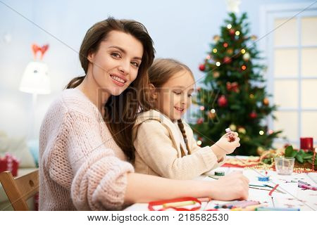 Attractive woman wearing knitted sweater looking at camera with warm smile while her adorable little daughter sitting on her laps and choosing decorations for her handmade Christmas card.