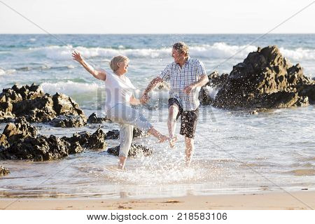 lovely senior mature couple on their 60s or 70s retired walking happy and relaxed on beach sea shore in romantic aging together and retirement husband and wife lifestyle concept