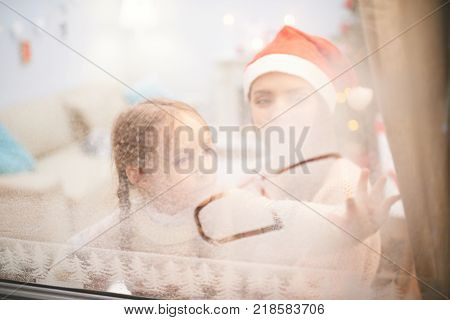 Cute little girl sitting on laps of her mother and drawing picture on frozen window with  forefinger, blurred background