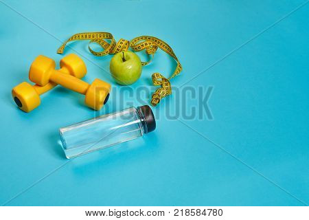 Dumbbells, centimeter, green apple, weight loss, healthy eating, healthy lifestyle concept on a blue background. Top view. Copy space. Still life. Flat lay