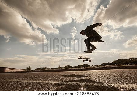 People youth urban lifestyle extreme sports and activity concept. Outdoor action shot of stylish young male in sneakers performing tricks using long board casting shadow of pavement. Warm filter