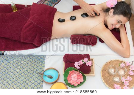 Asia beauty woman lying down on massage bed with traditional hot stones along the spine at Thai spa and wellness center so relax and lifestyle. Healthy Concept