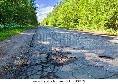 Dangerous pothole in the asphalt rural road. Road damage