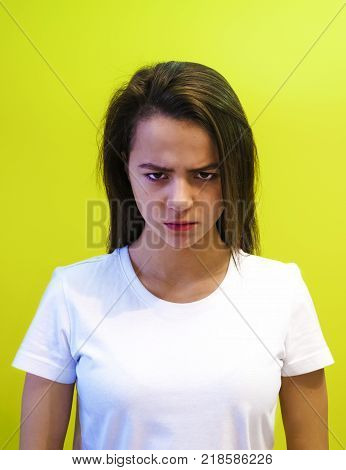 A serious unhappy teenager has an attractive appearance, sad after a quarrel with a loved one, frowns in discontent, isolated over the studio's yellow background. The concept of negative emotions.