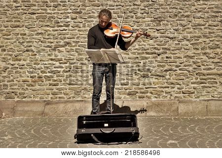 BRUGES BELGIUM - JUNE 10 2017: The street musician at an ancient stone wall. The man the musician plays a violin on the street of Bruges