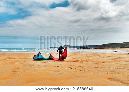 The athlete with windsurfing on the sandy beach. The windsurfer prepares on the beach about the ocean has developed and examines a sail