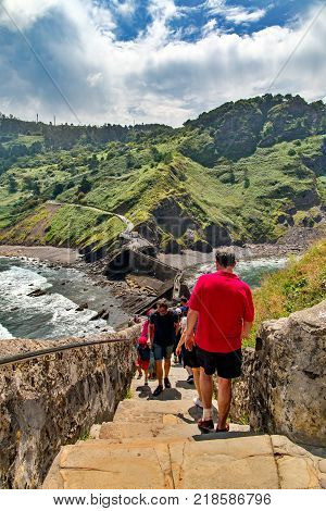 SAN JUAN DE GAZTELUGATXE SPAIN - JULY 4 2016: Tourists go on a stone ladder uphill. A long ladder to a chapel midday summer sun in the distance mountains and the ocean