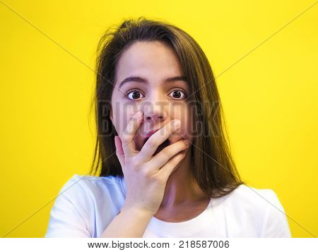 Portrait of surprised girl covering her mouth looking at the camera with stunned and shocked face expression while listening to some sensational news during conversation with her friend