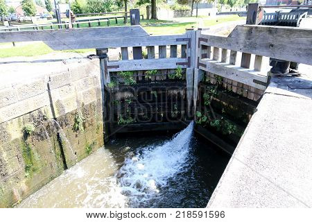 The water spurts through the large wooden doors of the lock on the canal