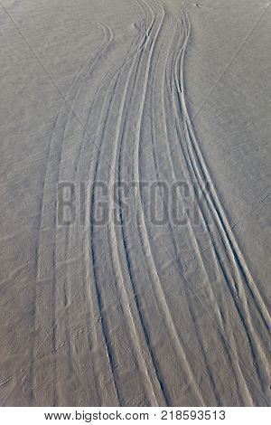 The snow and the traces on the surface of the ice on the river Lena in Ust-Kut in the winter. The surface of the snow with traces from wind and cars. Siberia Irkutsk region Russia.