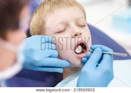 Male dentist examines the teeth of the patient cheerful child with blond hair. Boy smiling in dentist's chair with mouth wide open.