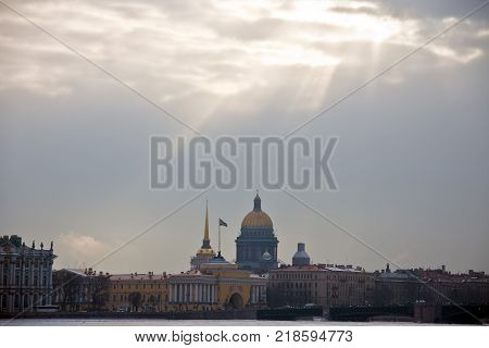 The sun's rays over the historical centre and the river Neva in St. Petersburg. The building of St. Isaac's Cathedral the Admiralty and the Palace bridge in winter.