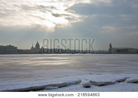 Rays of the winter sun over the river Neva in Saint-Petersburg. The historical center of St. Petersburg. Buildings palaces and promenades on the banks of the Neva