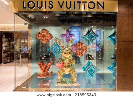 Paris France - October 30 2017: Showcase of famous designer bag brand Louis Vuitton in Printemps shopping centre in Paris. Festive christmas decorations are made by an artist Jeff Koons.