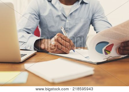 businessman reading documents in modern white office. Young unrecognizable  working man with papers, copy space