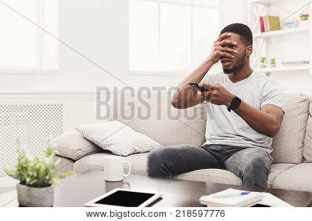 Young man wathing tv at home. Thrilled guy pointing with remote controller on tv-set, copy space