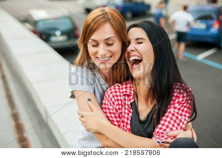 Two young teens hugging, laughting and sitting near road in the street. one brunette girl in red plaid shirt, another redhead girl wearing gray shirt and blue skirt. concept of sincere friendship