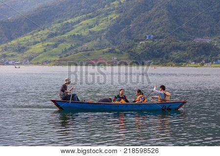 POKHARA NEPAL - September 29 2013: Tourists on old small boat sailing on the Phewa lake. Rowboat symbol of Phewa lakeside in Pokhara city.