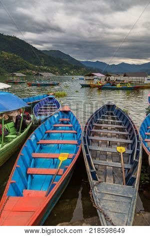 POKHARA NEPAL - September 29 2013: Resident on old small boats sailing on the Phewa lake. Rowboat symbol of Phewa lakeside in Pokhara city.