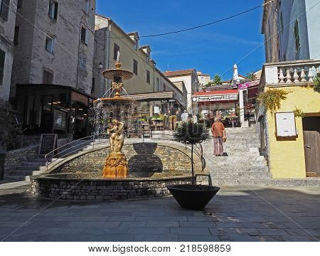 France Corse Corte June 21 2017 main street in corte city with fountain stairs old houses and walking people in summer