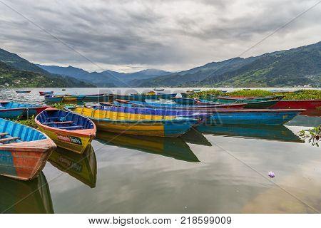 POKHARA NEPAL - September 29 2013: Old small boats on the Phewa lake. Rowboat symbol of Phewa lakeside in Pokhara city.