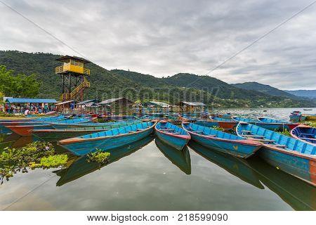 POKHARA NEPAL - September 29 2013: Tourist and old small boats on the Phewa lake. Rowboat symbol of Phewa lakeside in Pokhara city.