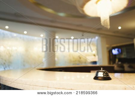 Hotel accommodation call bell on reception desk, contemporary interior, copy space poster