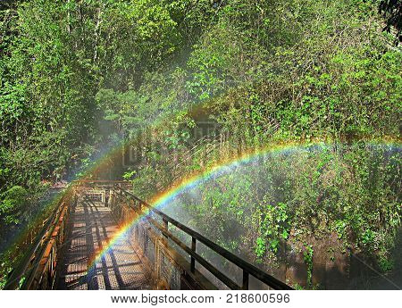 Two rainbows at a bridge near a waterfall called Salto Chico in Iguazu falls park Argentina one of the new seven wonders of nature and a UNESCO World Heritage site