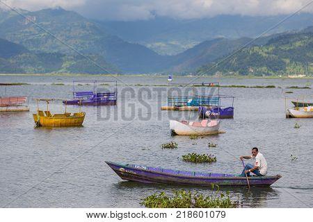 POKHARA NEPAL - September 29 2013: Tourists on old small boats sailing on the Phewa lake. Rowboat symbol of Phewa lakeside in Pokhara city.