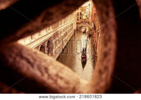 Venetian view from famous Bridge of Sighs at the Doge`s Palace in Venice, Italy. Bridge of Sighs is the way from the palace to the prison.