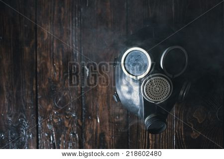 Gas mask on wooden background. Air pollution. Nature environment protection. Ecological catastrophe. Bio hazard concept