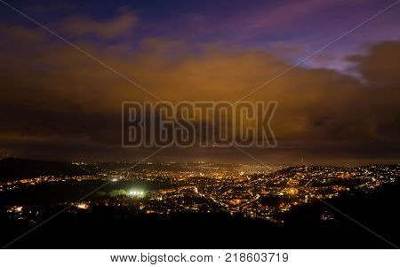 View of Bath at night from Solsbury Hill. The UNESCO World Heritage city seen nestling among hills from a high viewpoint under low clouds