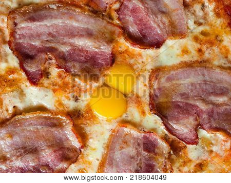 Carbonara pizza background with bacon and egg yolks. Delicious nourishing traditional recipe