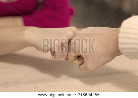 Female and male people giving a fist bump, Fist bump hand sign coherence
