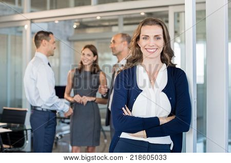 Portrait of executive businesswoman standing in office while team working in background. Smiling business woman leaning against glass wall looking at camera. Successful mature woman at work.