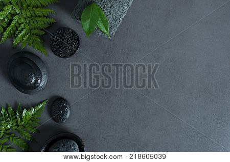 Top view of spa setting with wet hot stones and green ferns on gray background with copy sapce. High angle view of stacked black stones for massage with drops of water and rolled towel on blackboard.