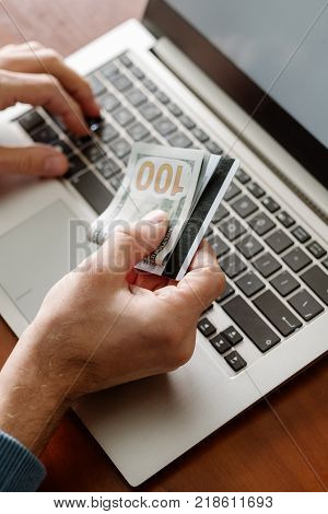 Online gambling. Man holding credit card and money reapy to play at internet casino on his laptop. Luck success and winning concept