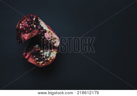 Ripe freshness red pomegranate with seed on dark background. Dissected pomegranate on pieces.