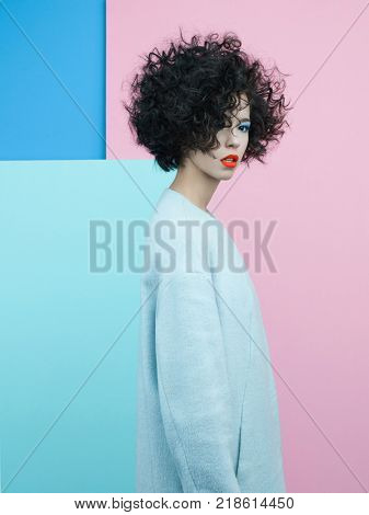 Studio fashion portrait of beautiful asian woman in sky-blue coat on colorful pastel background. Stylish look book. Autumn Winter season. Bright spring