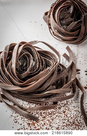 Raw unprepared chocolate pasta noodles. On a white kitchen marble table. Copy space