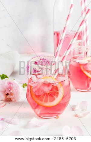 Summer refreshment drinks. Light pink rose cocktail with rose wine tea rose petals lemon. On a white stone concrete table. With striped pink tubules petals and rose flowers. Copy space
