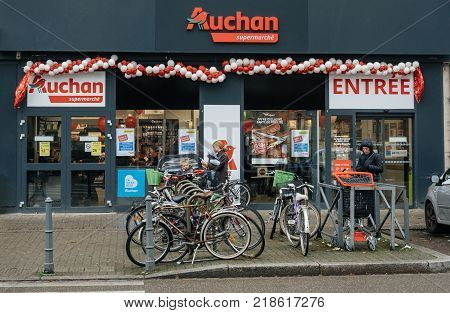 STRASBOURG FRANCE - DEC 4 2017: Auchan Supermarket entrance in French neighborhood on a winter snow day with customers exiting the entrance of the store