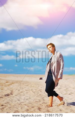 Portrait of a cute confident elegant model girl posing barefoot in an elegant coat in a Sunny day on a sandy beach on a blurred background of blue cloudy sky.