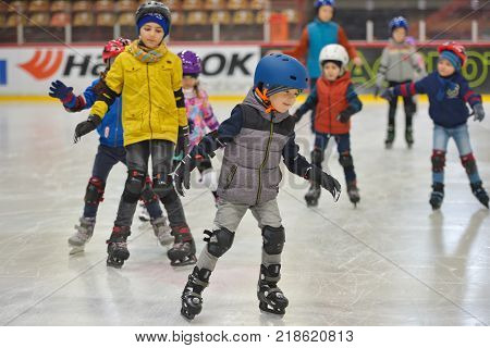 GALATI ROMANIA - DECEMBER 16 2017: Adorable little kisd in winter clothes with protections skating on ice rink
