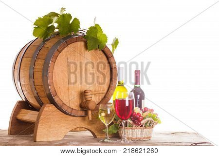 Grapes and bottels of wine near the wooden barrel. Glasses of wine on the table, concept of winery - red and white
