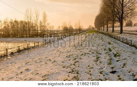 Overview of a snowy dike in a Dutch polder with fences and trees on both sides just before sunset.