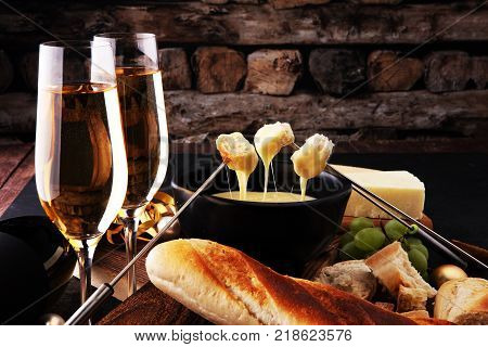 Gourmet Swiss fondue dinner on a winter evening alongside a heated pot of cheese fondue with two forks dipping bread and champagne