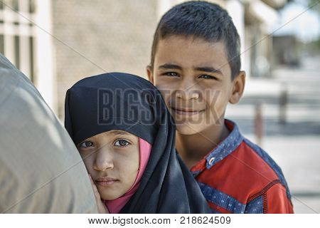 Yazd Iran - April 21 2017: Close-up portrait two Iranian children boy and girl of primary school age brother and sister.